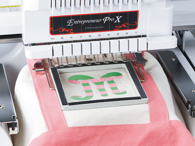 White and pink bag in clamp frame on embroidery machine